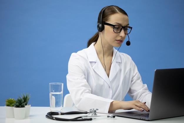 Consulta médica en línea. doctor atractivo en auriculares hablando con paciente