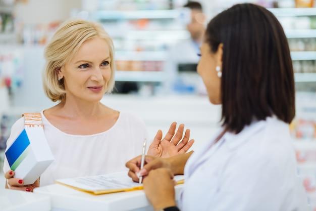 Consulta profesional. visitante senior alegre manteniendo una sonrisa en su rostro mientras habla con el químico internacional