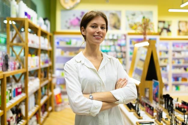 Consultor de chica atractiva con una camisa blanca se encuentra en la entrada de la tienda en la ventana de cosméticos
