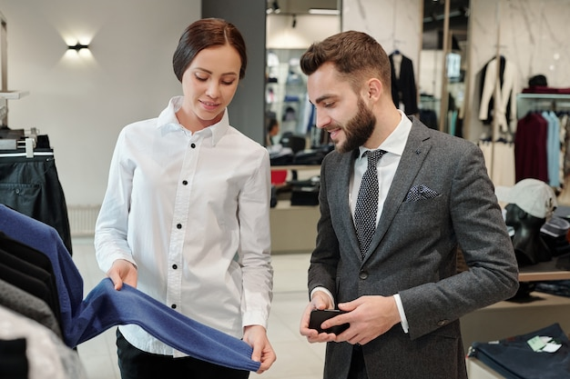 Consultor de cliente joven sonriente mostrando suéter mientras habla con el empresario en la tienda para hombres