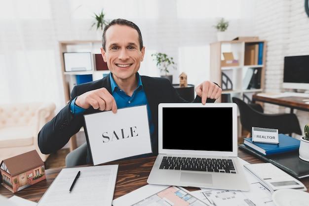 Consultor feliz con laptop real estate office.