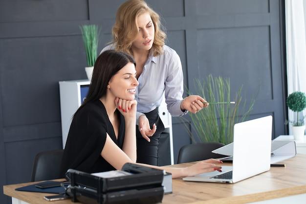 Consultor de inversiones de dos mujeres de negocios analizando el informe financiero anual de la empresa