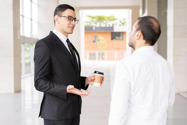 Consultor joven confidente hablando con el cliente en el pasillo de la oficina