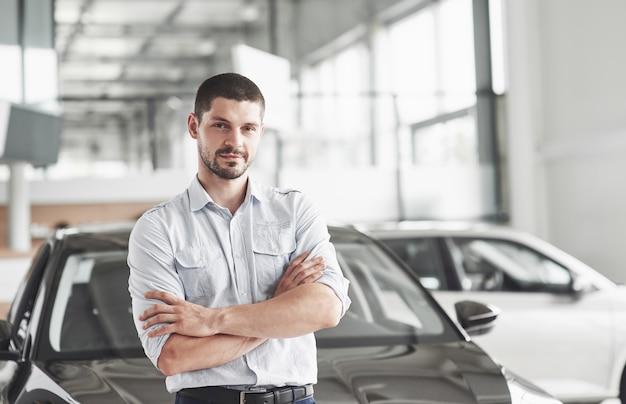 Consultor de joven guapo en el salón del coche de pie cerca del coche.