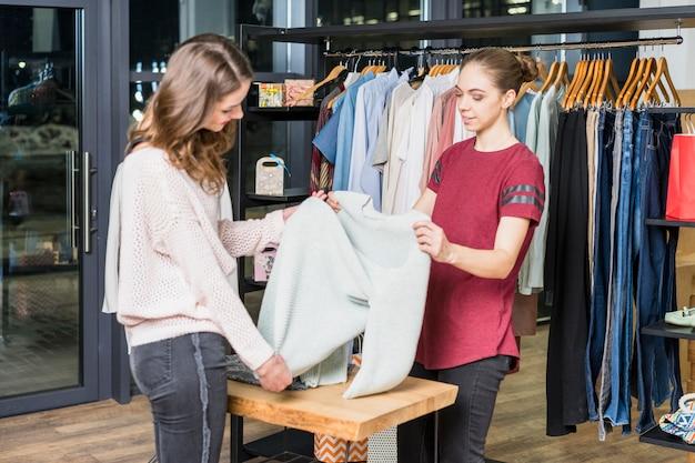Consultor joven mostrando ropa al cliente en centro comercial.