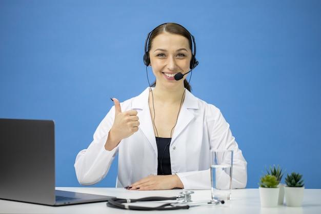 Consultor en línea femenino en bata blanca y auriculares sonriendo y mostrando como signo