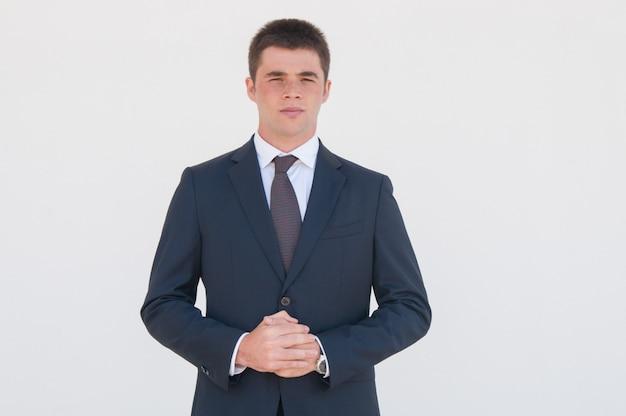 Consultor de negocios joven pensativo de pie para la cámara