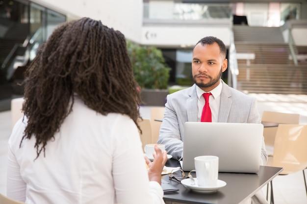 Consultor y reunión de clientes con una taza de café