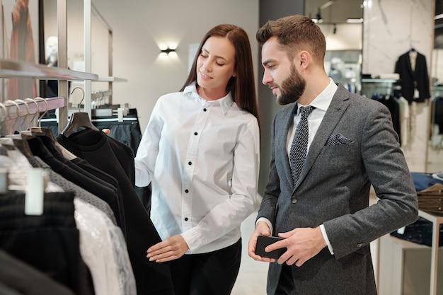 Consultora de moda morena en blusa blanca mostrando suéter al hombre mientras le da consejos en la tienda de ropa