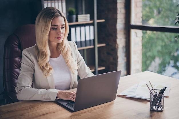 Consultora de negocios seria y reflexiva que navega a través de su computadora portátil en busca de nuevos clientes y clientes para ser reclutados