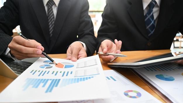 Consultoría empresarial con datos de análisis de dos hombres con dispositivo y documento en papel.