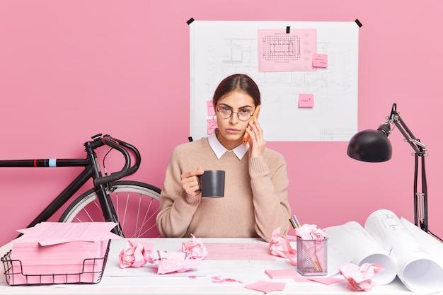 La consultoría de geys de joven empleada a través de poses de teléfonos inteligentes en el escritorio bebe posa de café en el escritorio con papeles arrugados alrededor prepara el proyecto de arquitecto comparte ideas para el inicio productividad