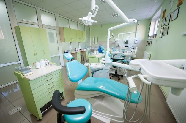 Consultorio dental contemporáneo vacío con tres sillas dentales y equipo