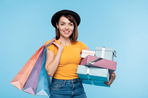 Consumidor alegre y satisfecho en ropa casual con bolsas de papel y pila de regalos después de la venta de temporada en el centro comercial