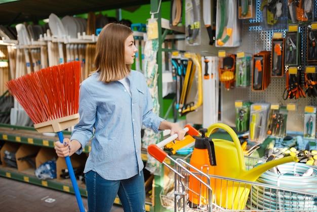 Consumidor femenino eligiendo herramientas, tienda para jardineros
