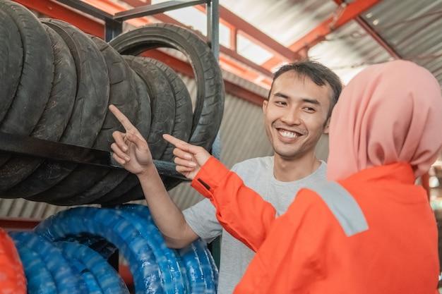 Consumidor masculino asiático mira un neumático apuntando con el dedo seleccionando un neumático con un mecánico femenino con velo en un taller de motos