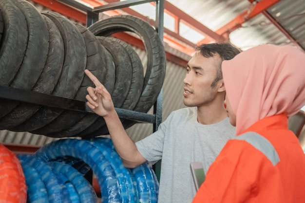 Consumidor masculino mira un neumático apuntando con el dedo seleccionando un neumático con un mecánico femenino con velo en un taller de repuestos de motos