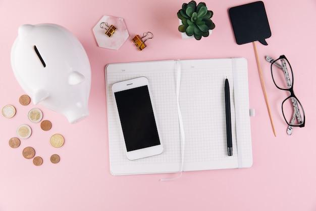 Contabilidad empresarial con ahorro de dinero, hucha, monedas, dinero, gafas y teléfono inteligente