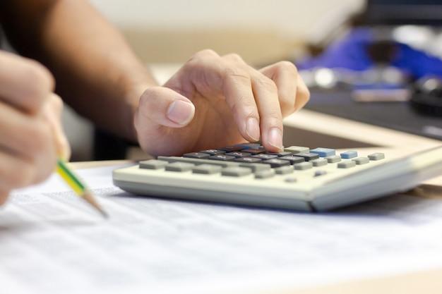 Contabilidad del hombre de negocios usando la calculadora para calcular finanzas y sostener el lápiz