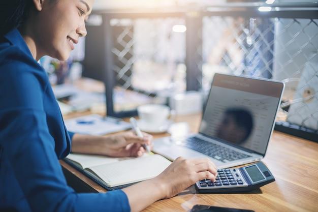 El contable de la mujer que trabaja usando la calculadora para calcula informe financiero en el lugar de trabajo.