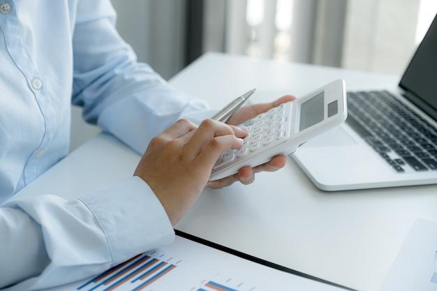Contable de mujeres empresarias utilizan calculadora y portátil haciendo cuenta para pagar impuestos en el escritorio blanco en la oficina de trabajo.