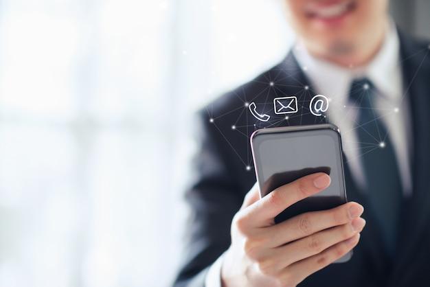 Contáctenos, feliz empresario sosteniendo teléfono inteligente móvil con iconos de correo, teléfono y correo electrónico