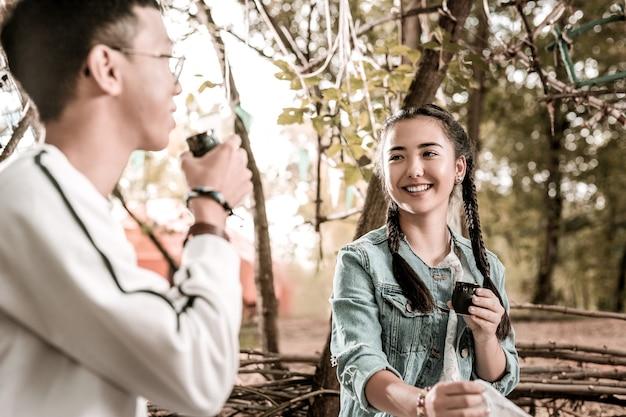Contacto visual. chica atractiva expresando positividad mientras va a tomar té