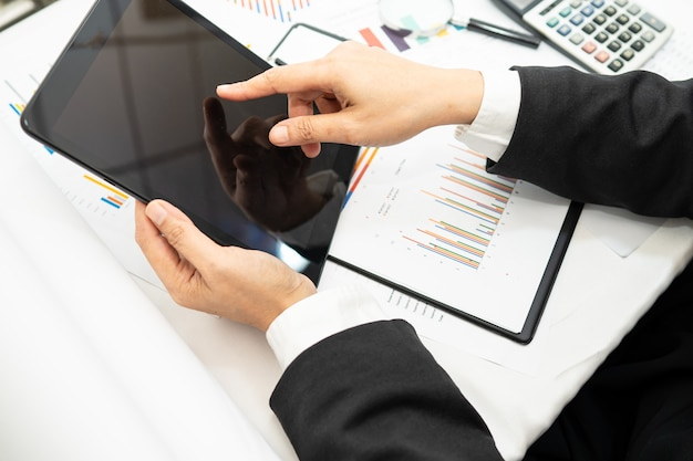 Contador asiático que trabaja y analiza la contabilidad del proyecto de informes financieros con el gráfico y la calculadora en la oficina moderna, las finanzas y el concepto empresarial.