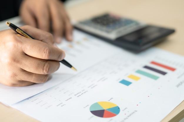 Contador asiático trabajando y analizando informes financieros