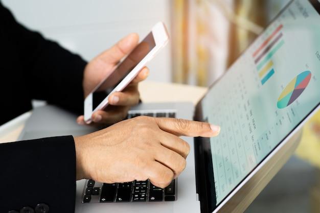 Contador asiático trabajando proyecto de informes financieros con gráfico.