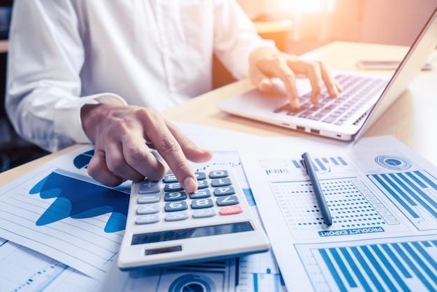 El contador del empresario o el experto financiero analizan el gráfico del informe comercial y el gráfico financiero en la oficina corporativa. concepto de economía financiera, negocio bancario e investigación bursátil.