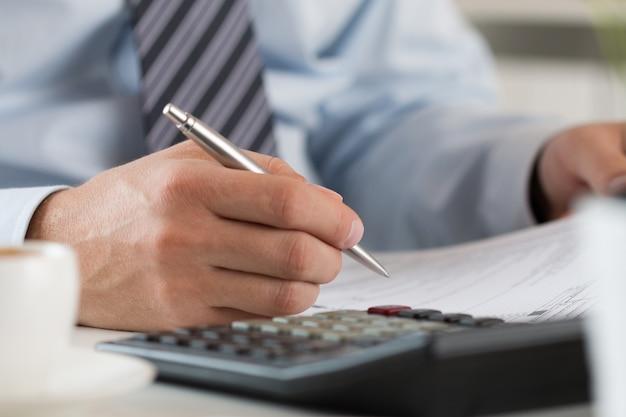 Contador haciendo cálculos, firmando contacto, cerrando saldo o haciendo informe financiero