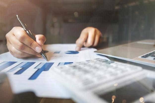 Contador / inspector financiero cálculo en la inversión de datos con documentos y portátil en la oficina oscura habitación