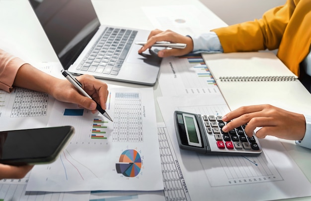 Contador de mano sosteniendo bolígrafo apuntando en la tabla de papeleo para la reunión del equipo en la sala de la oficina de cerca. concepto de finanzas y contabilidad