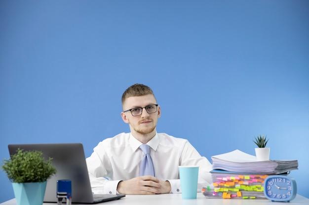 Contador masculino en la oficina mira atentamente copiar espacio en la pared azul