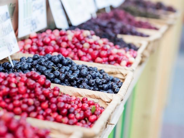 Contador en el mercado con una variedad de bayas maduras en bandejas de mimbre. temporada de verano.