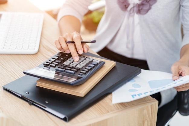 Contador de la mujer que trabaja en cuentas en análisis de negocio con gráficos y documento informe de datos financieros con computadora portátil en la oficina, concepto de negocio.
