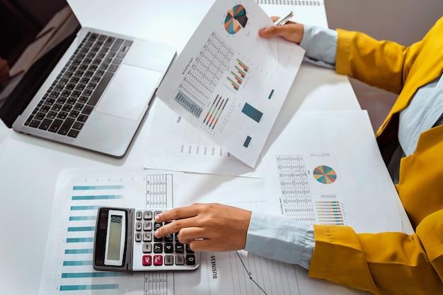 Contador de mujer usa calculadora y computadora con lápiz de sujeción en el escritorio en la oficina. concepto de finanzas y contabilidad