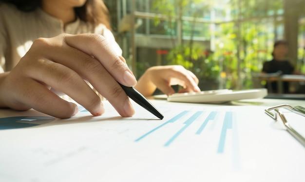 Contador las mujeres trabajadoras utilizan la calculadora con documento de hoja de cálculo, concepto de información financiera.
