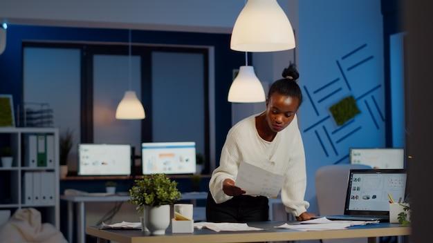 Contador negro que trabaja en informes financieros comprobando gráficos de estadísticas, mirando la computadora portátil, señalando los números de pie en el escritorio a altas horas de la noche en la oficina de puesta en marcha haciendo horas extraordinarias para respetar la fecha límite