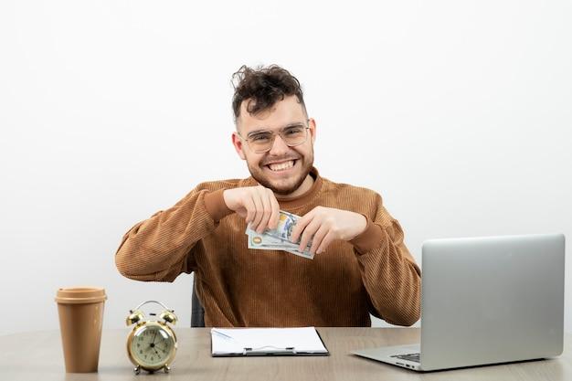 Contador de sexo masculino joven que se sienta en su escritorio y que muestra efectivo.