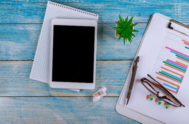 Los contadores trabajan analizando informes financieros en una tableta digital con auriculares inalámbricos y gafas