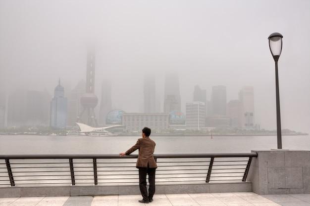 Contaminación del aire de shanghai, china, rascacielos envueltos en una densa niebla tóxica, el aire en la ciudad permaneció severamente contaminado, un hombre de pie en el bund y mira el distrito de pudong.