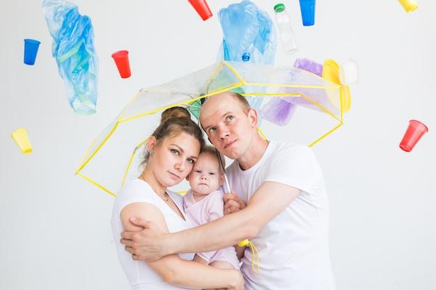 Contaminación ambiental, problema de reciclaje de plástico y concepto de eliminación de desechos: familia sorprendida debajo de la basura