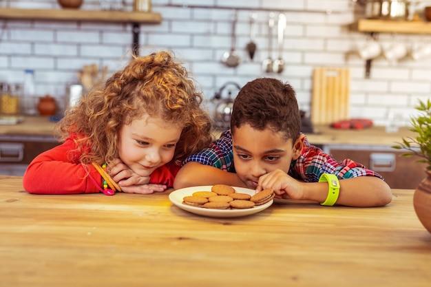 Contemos. niños alegres mirando galletas mientras van a comerlas después de la cena