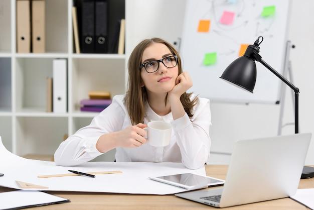 Contemplado arquitecto mujer sosteniendo una taza de café sentado en el lugar de trabajo