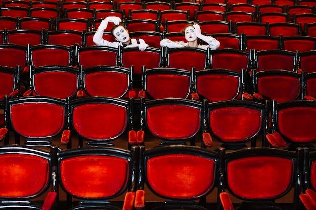Contemplado artista de mimo masculino y femenino sentado detrás de los sillones