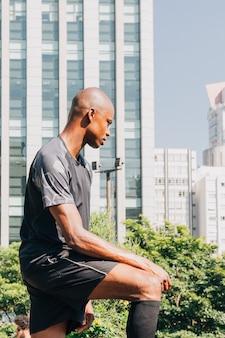 Contemplado joven atleta masculino de pie delante del edificio