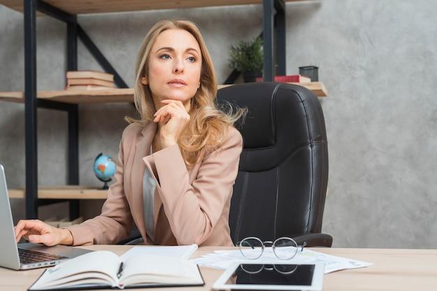 Contemplado joven empresaria con laptop; diario; tableta digital en escritorio de madera
