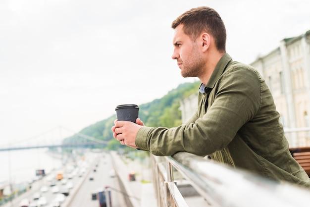 Contemplando al hombre joven que sostiene la taza de café disponible que mira la vista de la ciudad